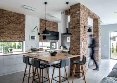 Pomysł na aranżację kuchni z wykorzystaniem drewnianego stołu.