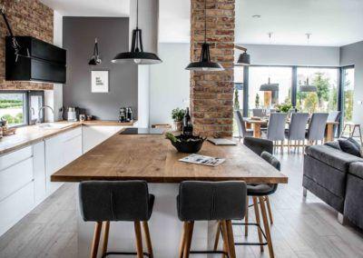 Przykładowy wystrój kuchennego wnętrza, w którym głównym elementem jest solidny drewniany stół.