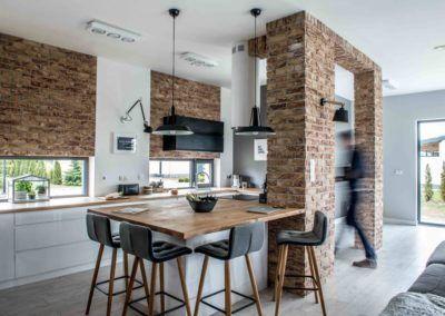 Projekt kuchni łączący w sobie biel, cegły, solidne lite drewno i nowoczesne dodatki.