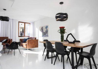 Przykład urządzenia nowoczesnego wnętrza z wykorzystaniem drewnianego stołu do jadalni.