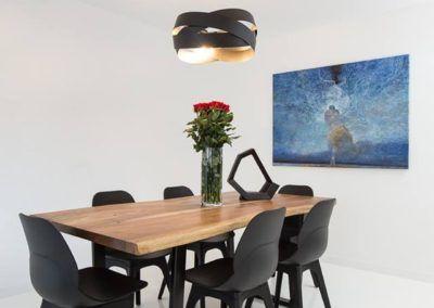 Aranżacja jadalni, w której wykorzystano nowoczesny drewniany stół i stylowe, dopasowane krzesła.