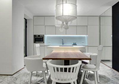 Stół z drewna litego jako dominujący element umeblowania w nowoczesnej, białej jadalni.