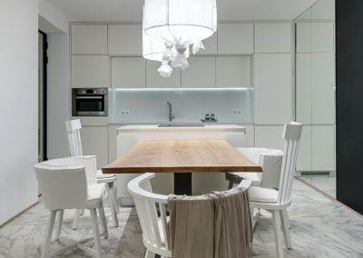 Przestronna, jasna kuchnia w odcieniach bieli, w której główny element stanowi nowoczesny, drewniany stół.