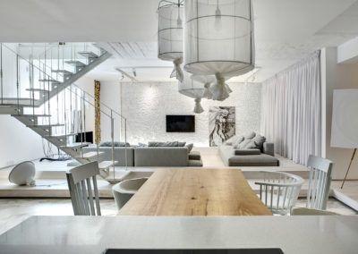 Drewniany stół widziany od strony kuchni, w tle nowoczesny salon w odcieniach bieli i szarości.