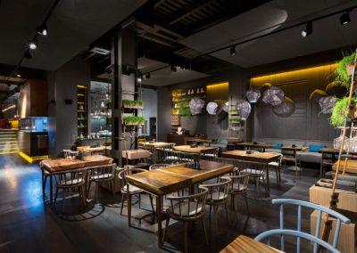 Przykład wykorzystania stołów drewnianych jako wyposażenia nowoczesnej restauracji.