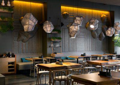 Pomysł na wykorzystanie drewna w wystroju restauracji - stoły z drewna litego i drewniana zabudowa.